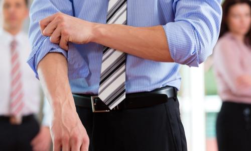 businessman rolling up shirt sleeves