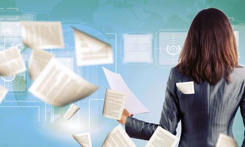 businesswoman surrounded by a swirl of papers and digital documents