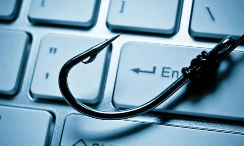 fish hook lying on a computer keyboard