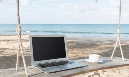 laptop and coffee cup on a swing by the beach