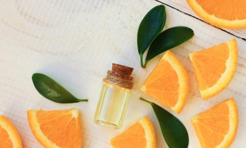 orange slices with a vial of essential oil and fragrant leaves