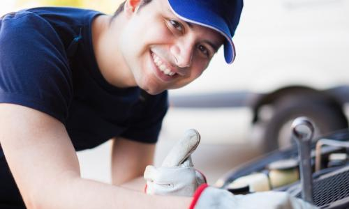 smiling mechanic tunes up a car engine