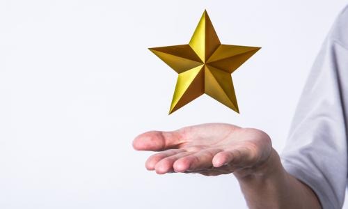 golden star hovering over a man's palm