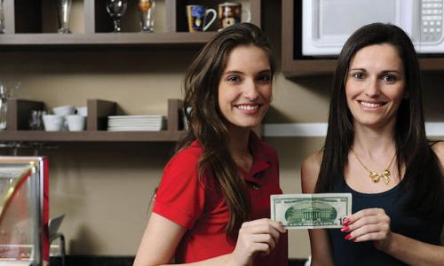 Two women each hold one corner of a dollar bill