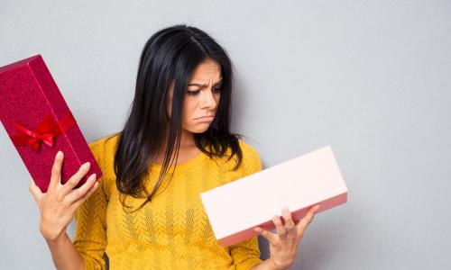 young woman in yellow sweater looking sadly into an open holiday gift box