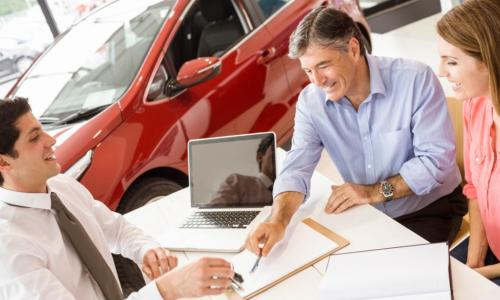 customers and car salesman at dealership desk signing papers