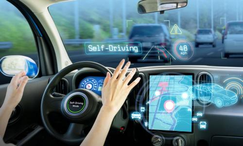 woman at steering wheel with self driving mode on her car's screen