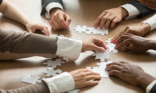 diverse group of business people putting together a puzzle on a table