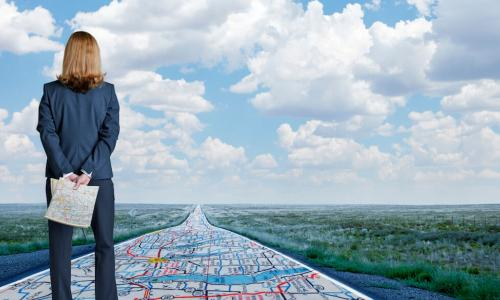 Professional woman stands on a map leading forward