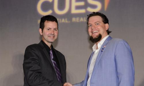 2017 CUES NTCUE winner Geoff Bullock shakes hands with Tim McAlpine of Currency Marketing
