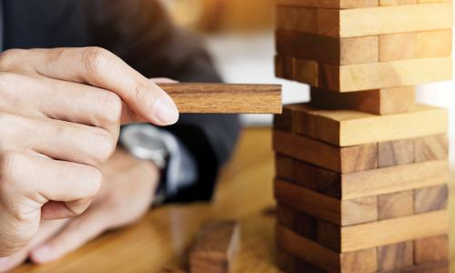 businessman carefully playing Jenga