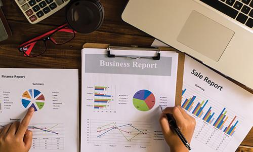 Person reviewing business reports with graphs and charts at a desk