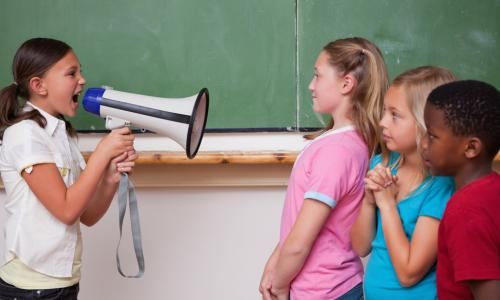 Young girl yelling orders through megaphone at classmates
