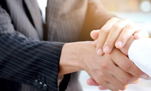 lender warmly shaking hands with business owner
