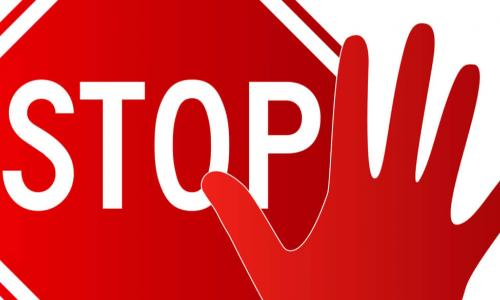 stop sign and red hand held up in a stop motion