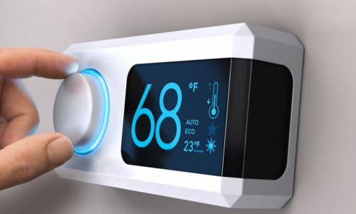 hand adjusting a digital thermostat set to 68 degrees
