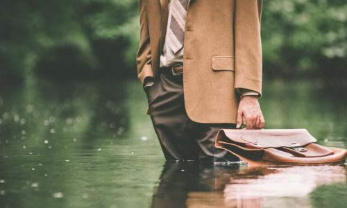 Businessman stands in flood with briefcase