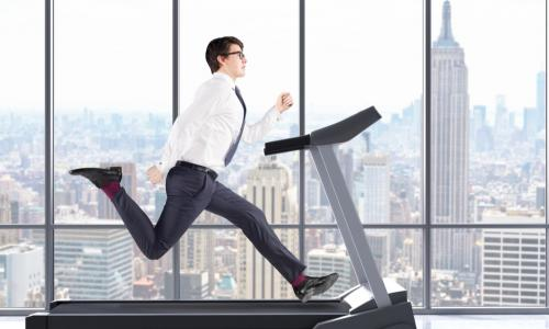 businessman running on a treadmill at a fast pace
