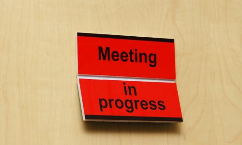 Sign on closed door reads Meeting in Progress