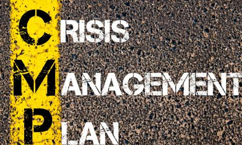 CRISIS MANAGEMENT PLAN painted on an asphalt road