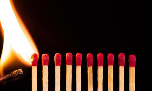 lit match igniting a line of matches