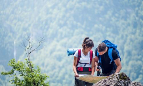 young male and female hikers using a map to navigate