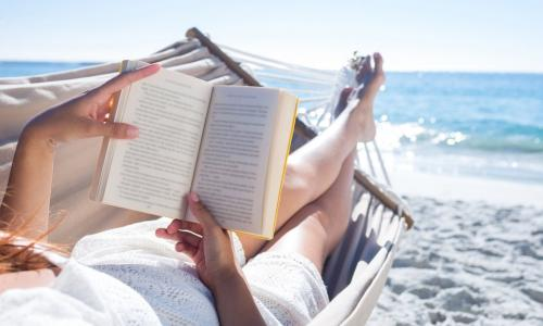 woman reading on the beach in a hammock