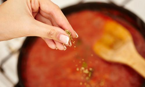 Hand adding ingredients to a tomato sauce