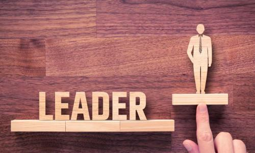 hand pushing a wood figure of a businessman up above the word leader