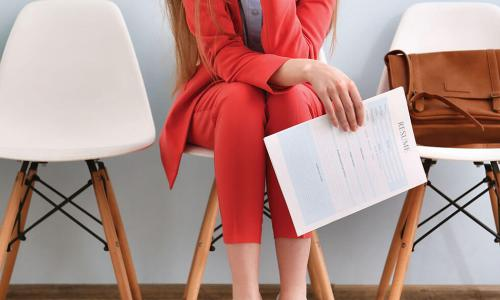 Woman in a red pantsuit sits on a white chair holding her resume while she waits for a job interview