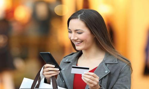 happy woman holding credit card and shopping bags while looking at smartphone