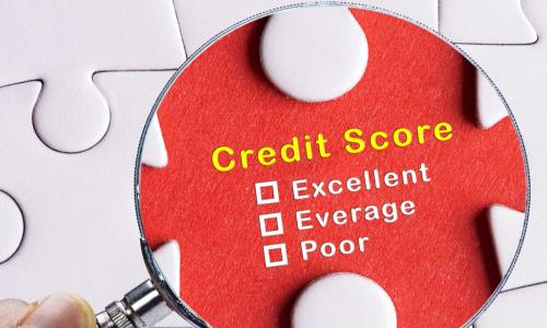 a magnifying glass focusing on the words credit score on a puzzle piece in a larger white puzzle