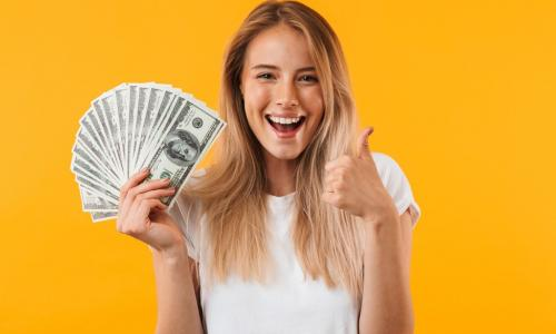 woman on a yellow background holding fanned out money
