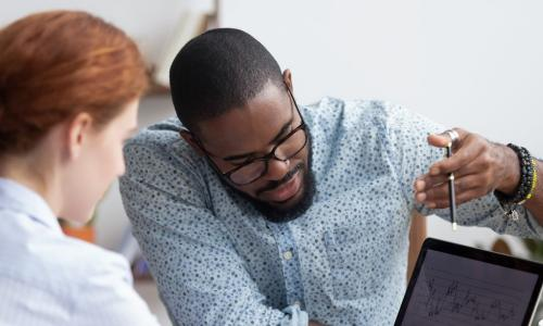 African-American man teaching a red-headed women over a computer