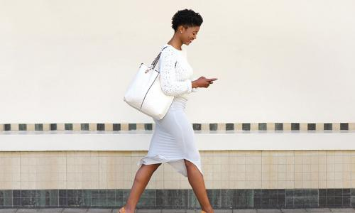 happy young woman walking and texting