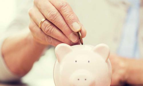 older woman's hand putting a coin into a piggy bank