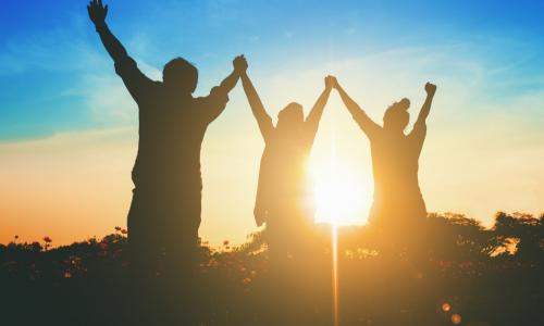 three people with their arms up to the sky with the glow of the sun