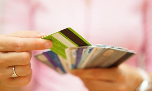 woman in pink choosing one card from a stack