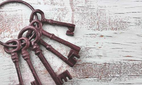 ring of old iron keys on a white wooden background