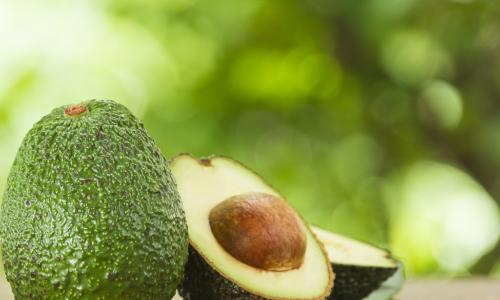 whole unripe avocado next to a ripe avocado sliced in half with pit showing