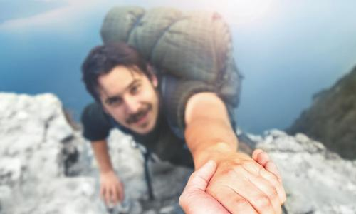 backpacker reaches up to helping hand