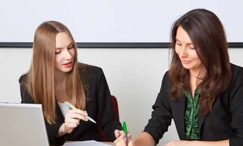 Two business women work with documents
