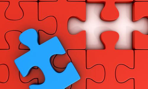 red puzzle pieces forming a perfect gap for the blue puzzle piece on top of them