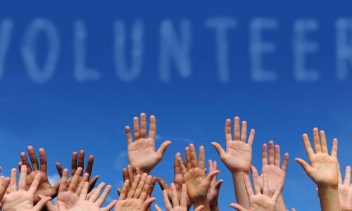group of hands on a blue sky background with the word volunteer above them