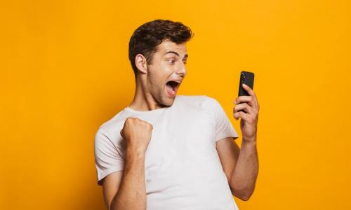 ecstatic young man with cell phone