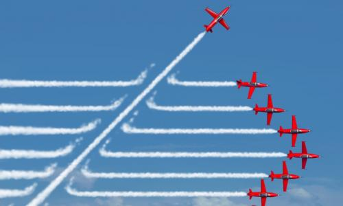 red planes flying in a straight formation with jet streams behind with one plane cutting through on a diagonal