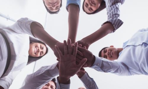 circle of businesspeople putting their hands together in the middle to signify teamwork and support