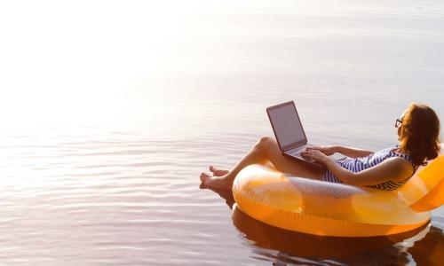 female workaholic using laptop while floating on a lake