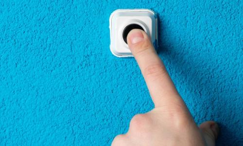 finger pressing doorbell on a blue wall