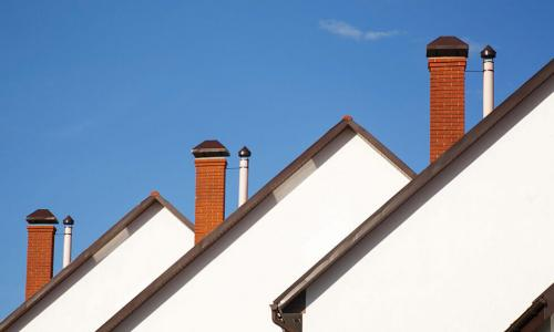 three white houses with brick chimneys in a row against a blue sky